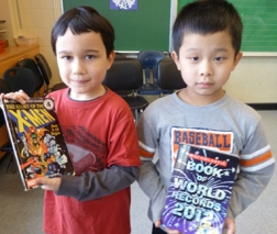 "Grade 1 students Matthew and Derek (left to right) proudly display the books they chose to take home with them. ""The cover is very cool,"" says Matthew. ""I think this book is good,"" says Derek. Photos by Julie Cheng"