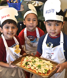 Chefs Jeevan, Nathan and Aezen proudly display their pizza masterpiece. Photo by Michelle Fattore